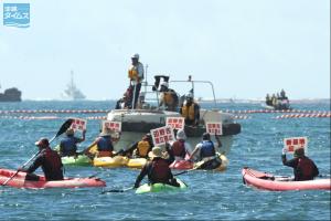 カヌーで沖合にこぎ出し基地建設に抗議する市民ら。 海上保安庁のゴムボートが立ちふさがる